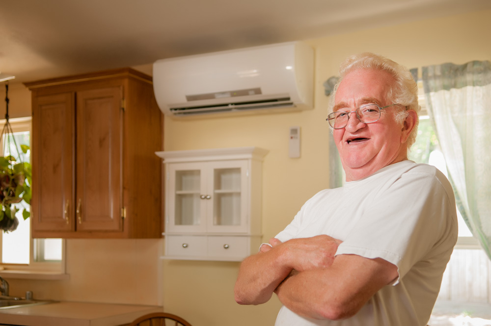 Man standing in his kitchen smiling. A ductless cooling system is behind him.