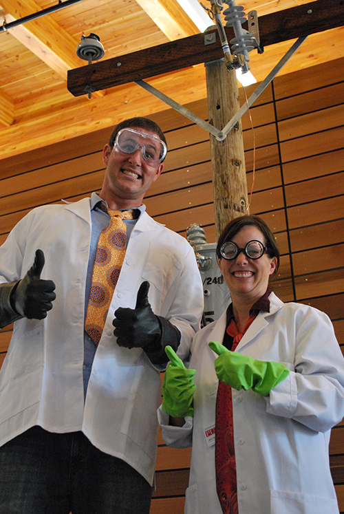 "A man and a woman wearing goggles and giving the ""thumbs-up"" hand sign."