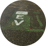 A painting on pavement of a gas pump with the letters EV on the front.