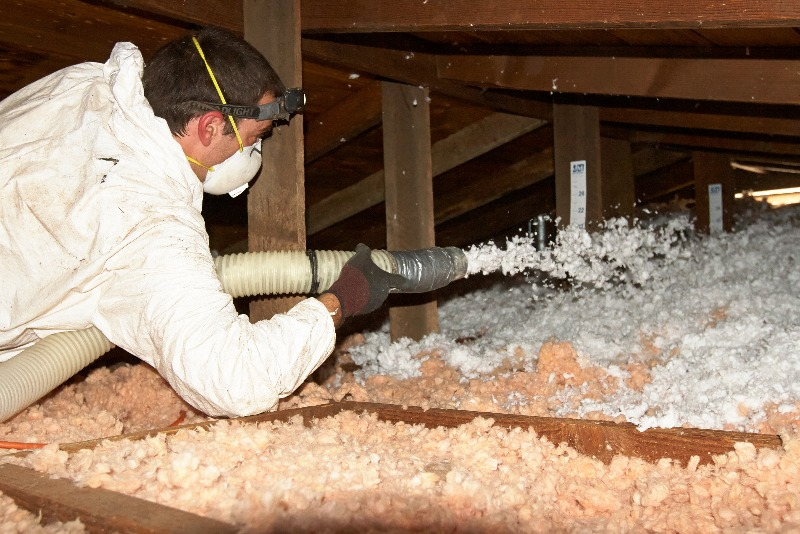 A man wearing a protective suit and mask adding insulation to an attic.